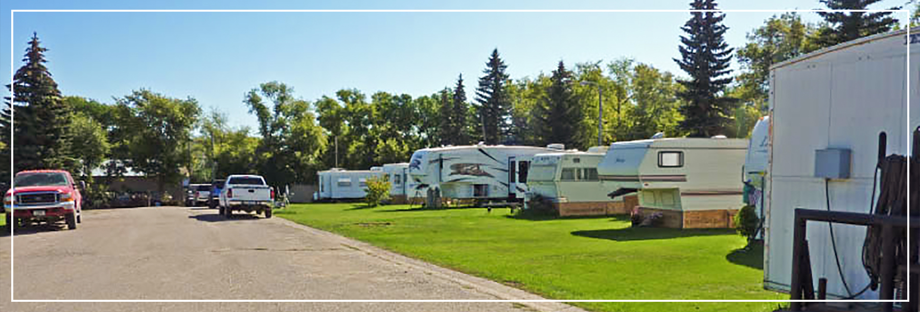 A summer time photo of several RVs on one of the lots of Stonehouse RV Park, in Stanley North Dakota.